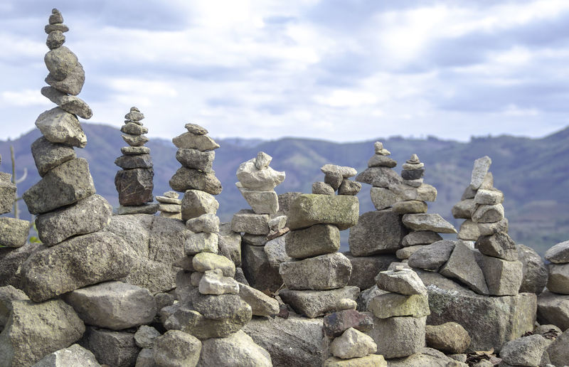 Stone stack on rocks against sky