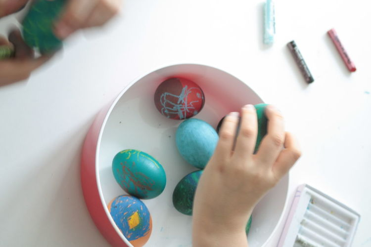Cropped Image Of Hand Holding Painted Eggs On Table