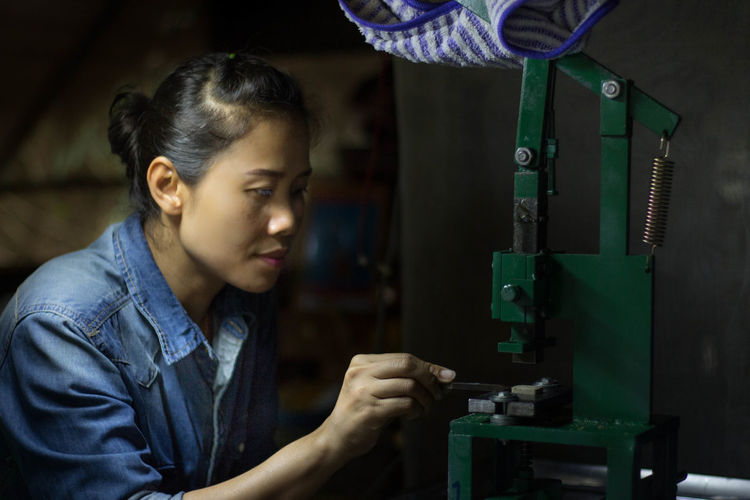 Asian girls doing some work Adult Close-up Day Headshot Indoors  Industry Machinery Manufacturing Equipment Occupation One Person People Real People Technology Working Workshop Young Adult Young Women