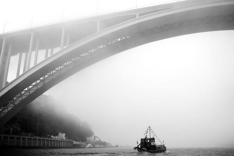 Arrabida bridge below trawler sailing on douro river in foggy weather