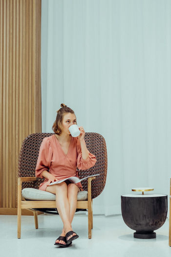 Young caucasian millennial woman sitting in a modern armchair reading and drinking hot beverage.