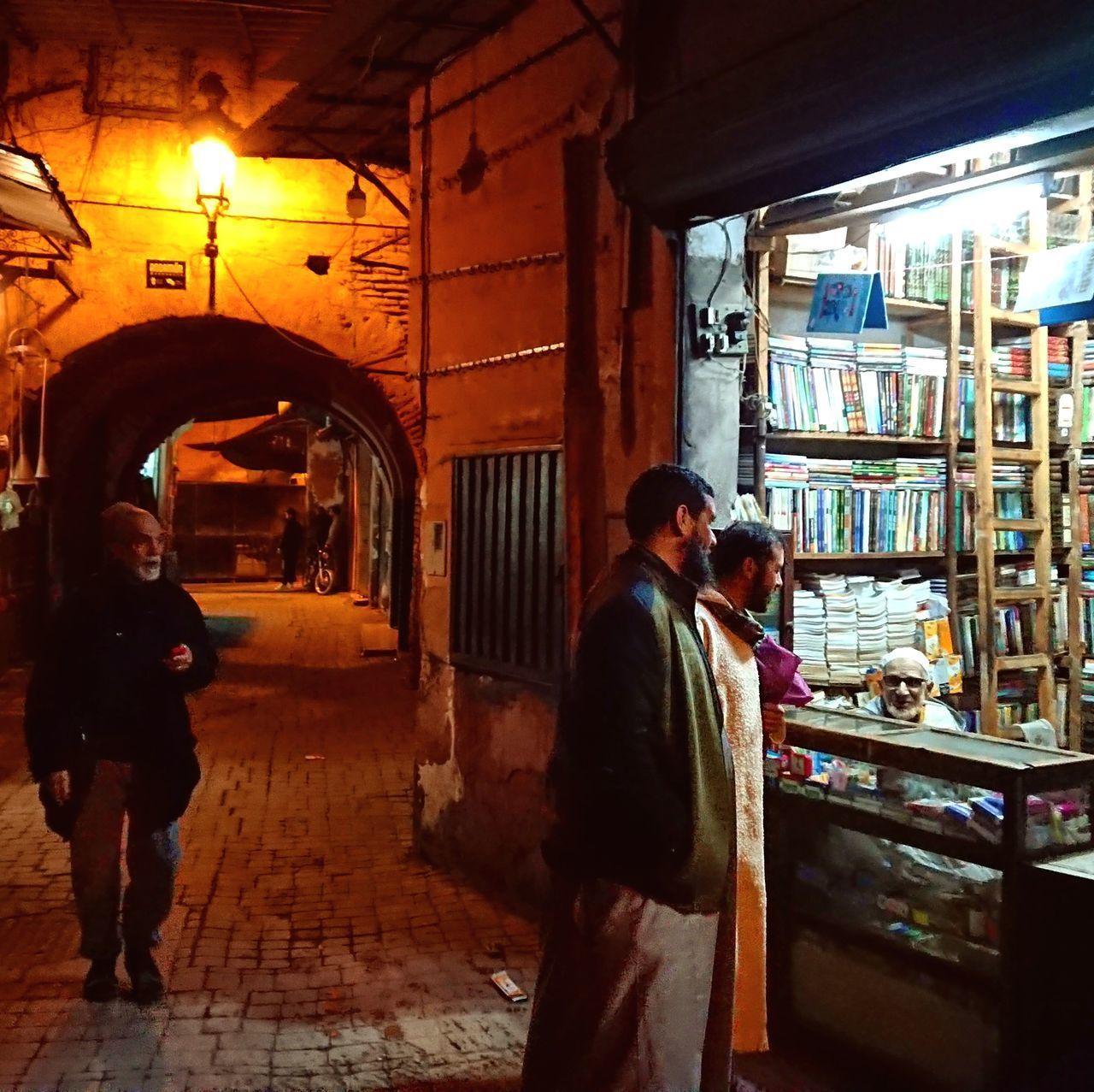 FULL LENGTH OF MAN STANDING ON STREET IN ILLUMINATED CITY