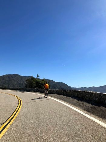 Biker going up a mountain road today in the bright morning sun. Sky Road Transportation Mountain One Person Day Nature Road Marking Symbol Full Length Real People Men Leisure Activity Lifestyles Blue Marking Copy Space The Way Forward Direction Sign Go Higher Inner Power Go Higher