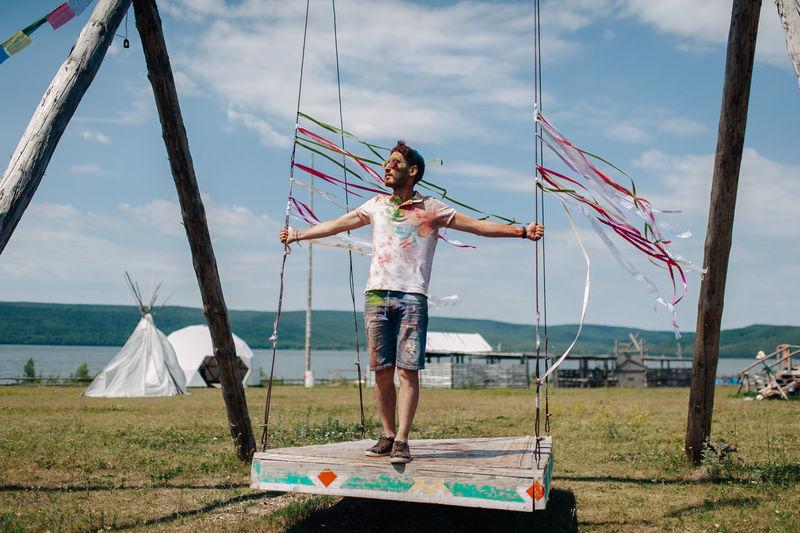 Man standing on swing over land against sky