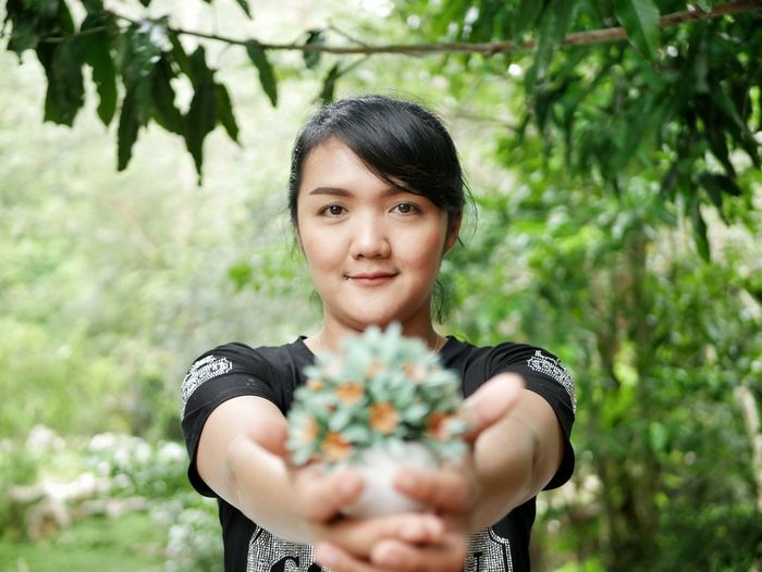 Portrait Of Young Woman Holding Plants