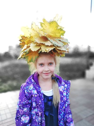 Portrait Of Smiling Girl With Autumn Leaves On Head