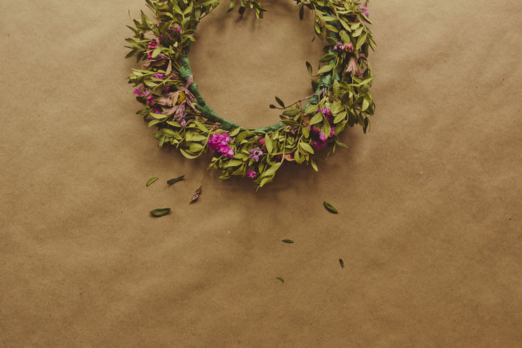 High angle view of floral wreath on brown paper