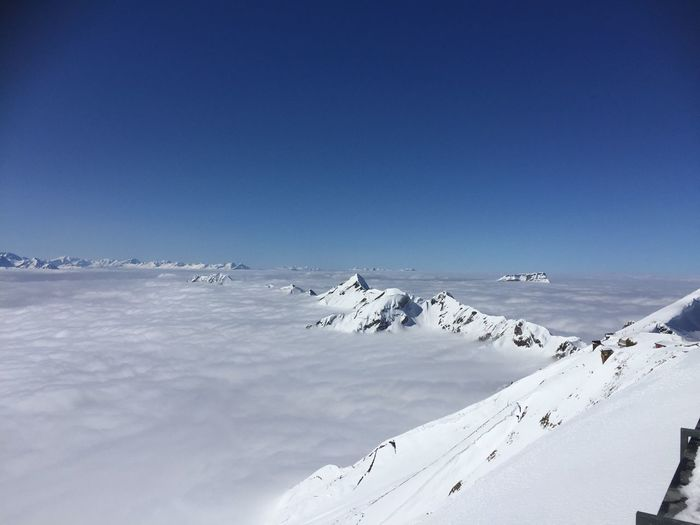 Scenic view of snow covered mountain against blue sky