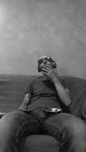 Man Smoking Cigarette While Sitting On Couch