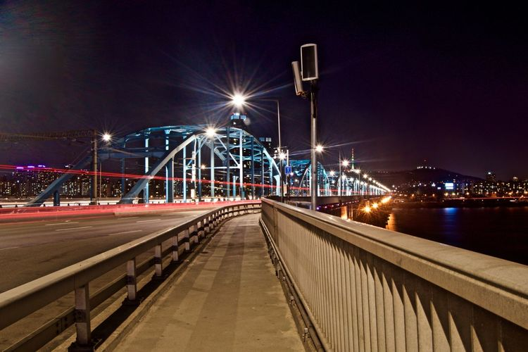 Architecture Bridge - Man Made Structure Building Exterior City Cityscape Connection Downtown District Illuminated Light Trail Long Exposure Neon Night No People Outdoors River Road Sky Street Light Suspension Bridge Transportation Travel Destinations Urban Road Water