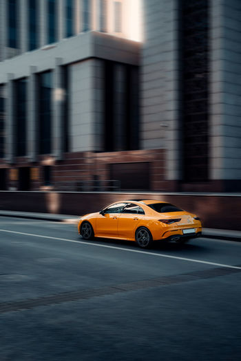 Blurred motion of yellow car on road