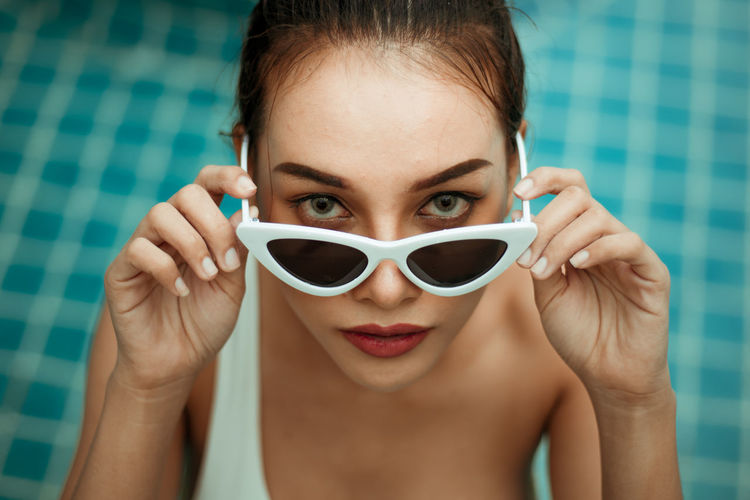 High angle portrait of young woman wearing sunglasses in swimming pool