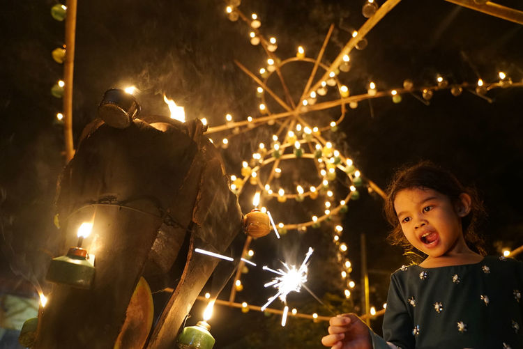 Low angle view of happy girl holding sparkler