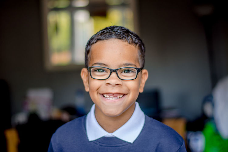 Close-up portrait of happy boy wearing eyeglasses while standing at home