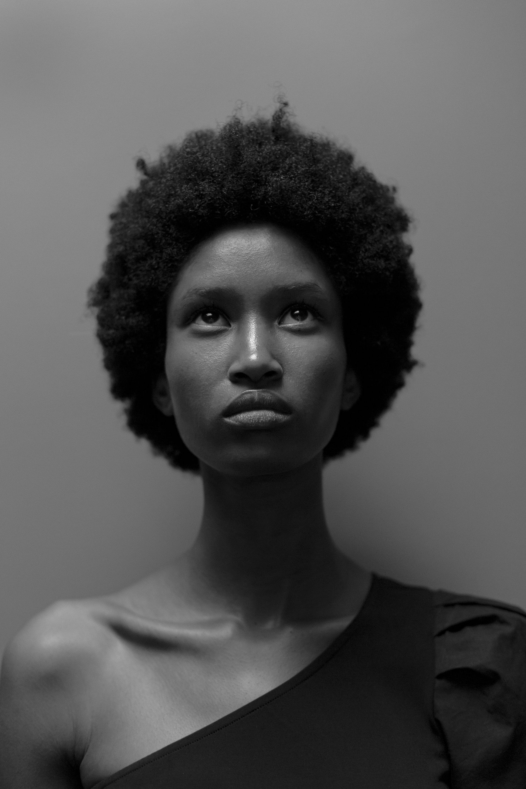 black, portrait, afro, curly hair, black and white, hairstyle, one person, human hair, studio shot, headshot, white, adult, monochrome, young adult, indoors, monochrome photography, looking at camera, front view, women, serious, gray background, individuality, fashion, gray, short hair, human face, close-up, person, looking