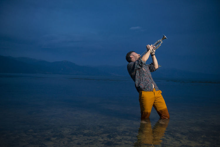 Man playing trumpet while standing in sea at night