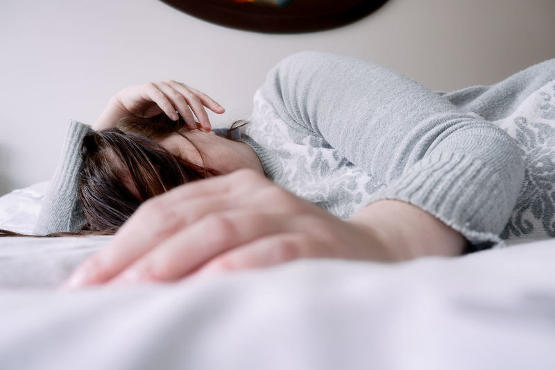 Midsection of woman sleeping on bed at home