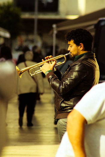 Side view of mature man playing trumpet on footpath at night