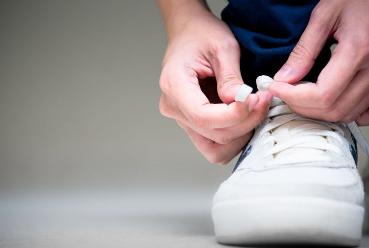 Low section of person tying shoelace