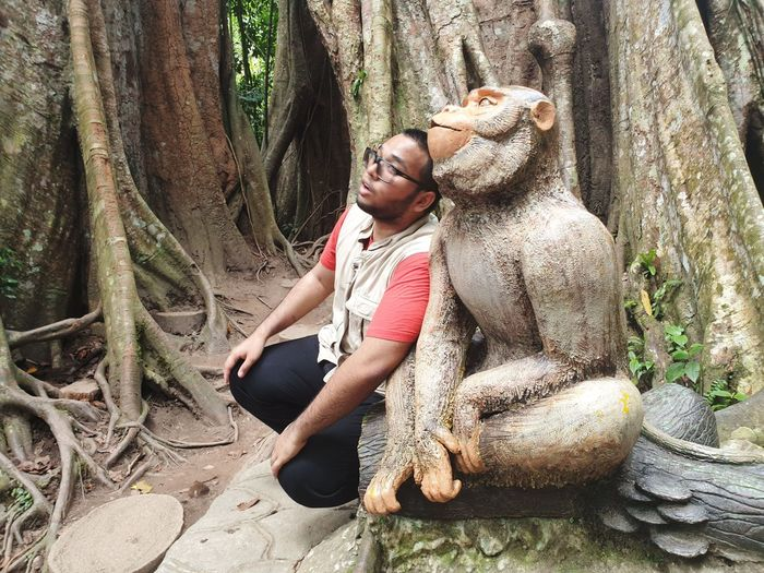 Young man sitting by statue against tree trunk in forest