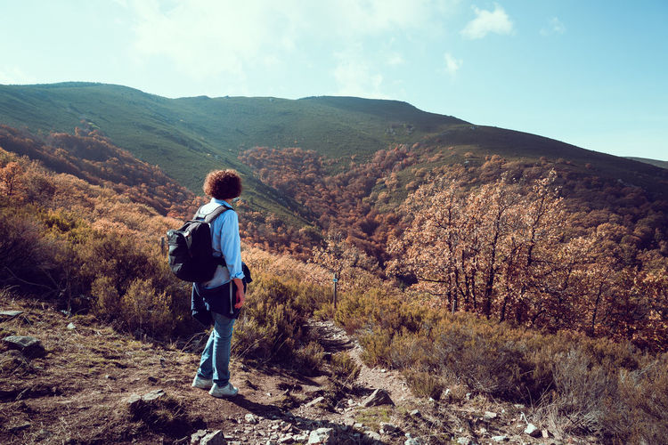 Full Length Of Backpacker Looking At Mountains Against Sky