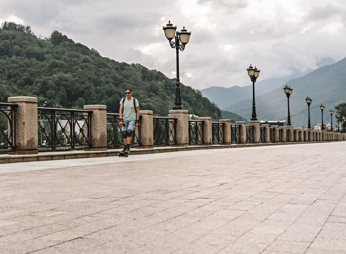 Young man in protective equipment riding on roller skates along embankment against  forest mountains