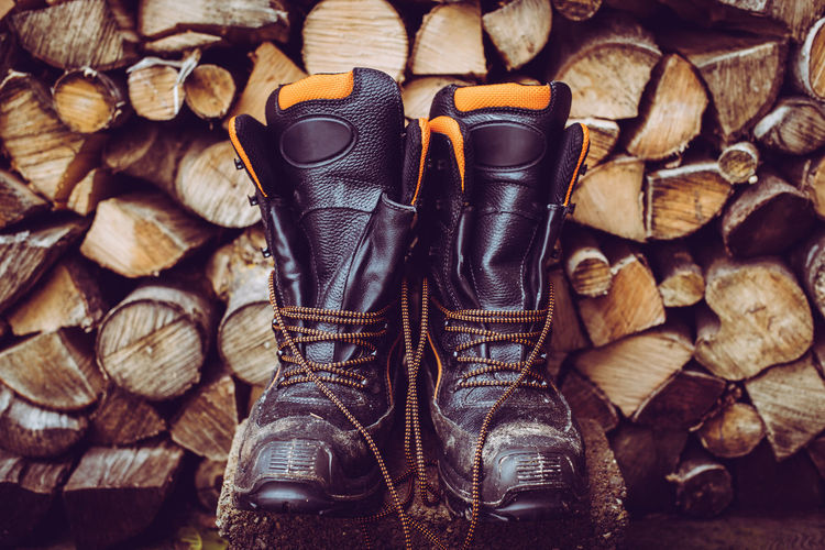 Woodcutter boots and stack of firewood woodcutter equipment and tools hard work outdoor
