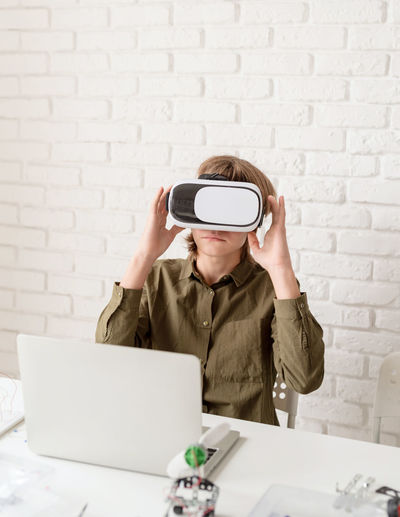 Nice teen boy in vr glasses sitting at the table playing game