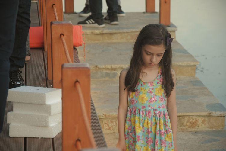Full length of girl standing against wall