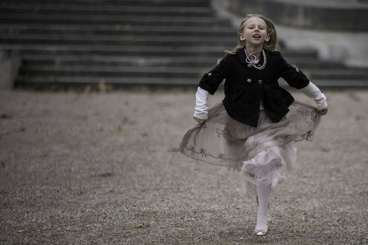 Stylishly and fashionably dressed girl in a dynamic photo while running against an antique