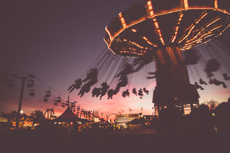 Low Angle View Of Chain Swing Ride At Sunset