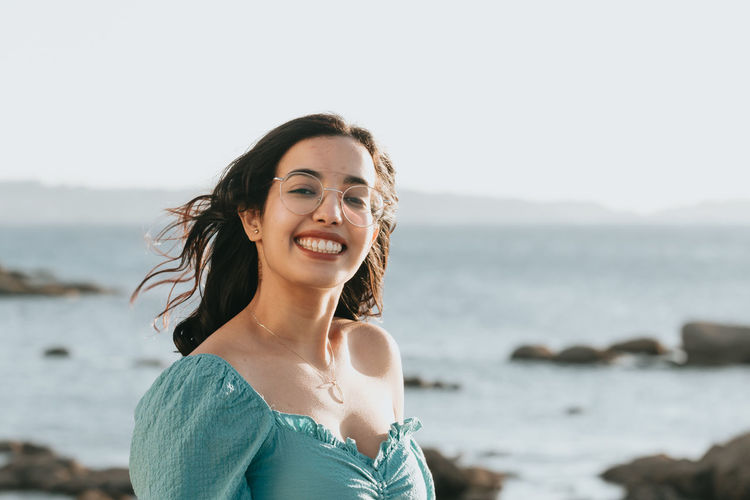 Portrait of smiling young woman at beach against sky