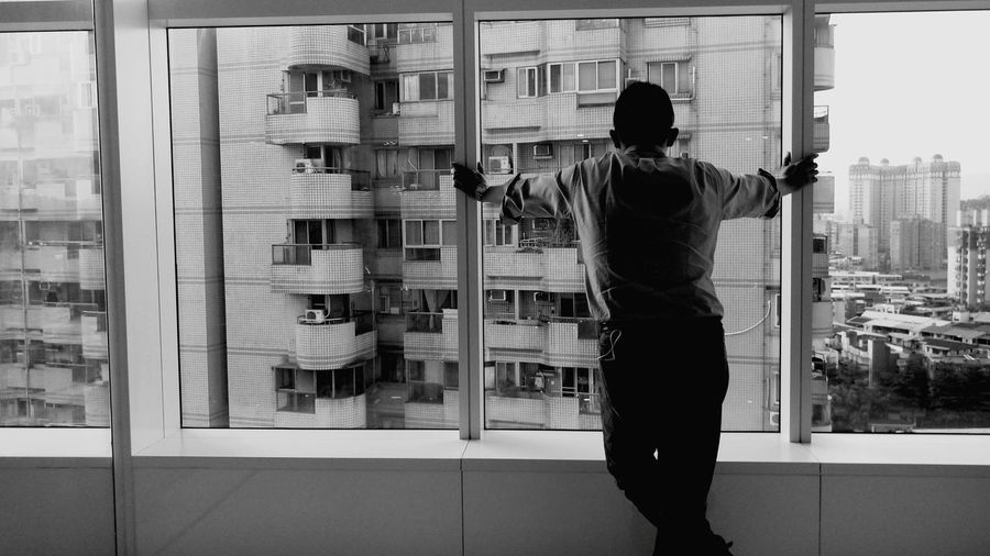 Man standing against window
