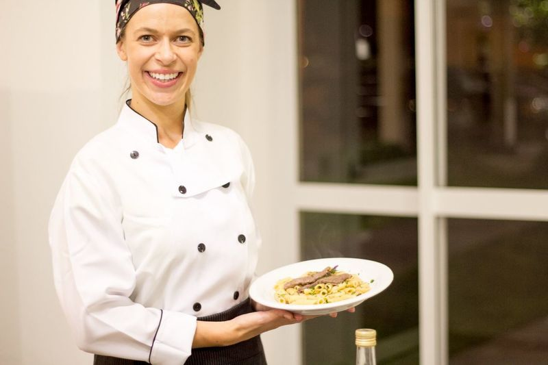 Portrait of happy female chef holding pasta in plate while standing in commercial kitchen