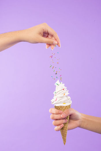 Cropped hands sprinkling sprinkles on ice cream against purple background