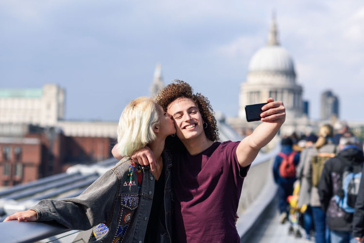 Happy couple taking a selfie photograph on London's Millennium Bridge, River Thames Architecture Two People Young Adult Togetherness Women City Young Women Lifestyles Built Structure Smiling Leisure Activity Emotion Adult Tourism Building Exterior Casual Clothing Real People Friendship Hair Outdoors Couple - Relationship Hairstyle