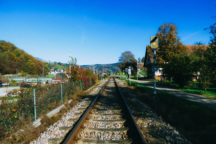 View of railroad tracks against clear blue sky