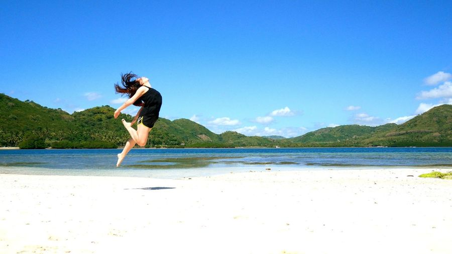 Full length of young woman jumping at beach against sky