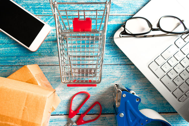 Online business concept. Shopping cart with boxes and smartphone on table Cost Web Credit Bag Banking Economy Consumer Express Catalog Consumers Logistics Electronic Packaging Keyboard Activities Promotion Concept Using Home International Shipping  Retail  Computer Order E-commerce Business Smartphone Online  Internet Cart Purchase Mobile Box Store Customer  Technology Shop Sale Delivery Buy White Marketing Commerce Payment Basket Space Top Accessories Lifestyle Background