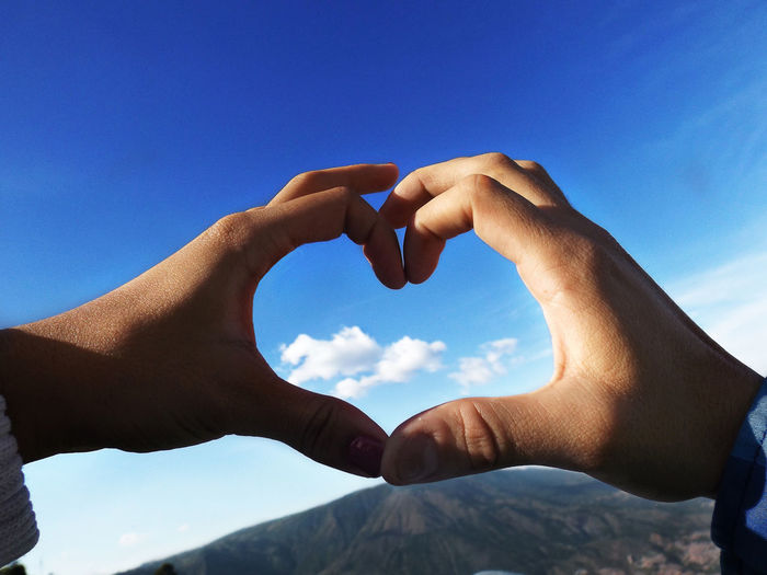 Close-up of hands making heart shape against blue sky