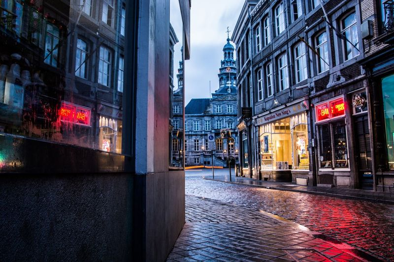 A challenge 😅 I wanted a composition with a Sin City, night crawler feeling. I left the colors in because of the red light (reflection) Maastricht Netherlands City Sin City Night City Hall Landmark Streetphotography Traveling Travel Photography Reflection Window Light Red Light