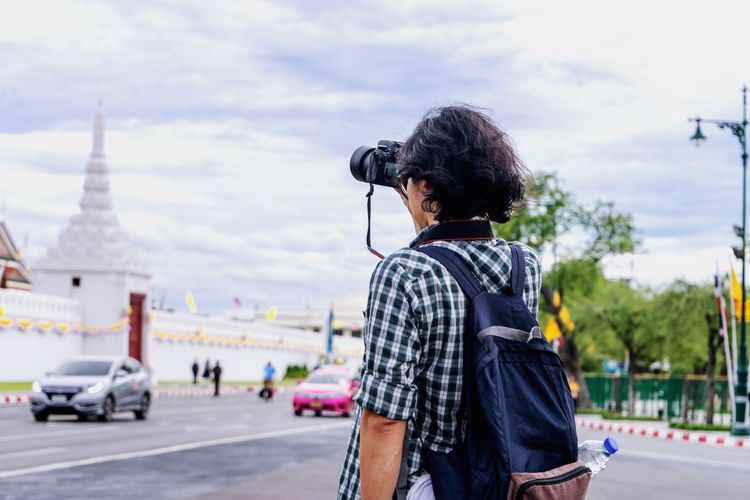 Rear view of man photographing against sky in city