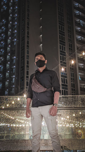 Full length of man standing at illuminated city at night