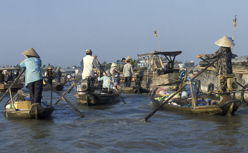 Vendor oaring boat in river against clear sky