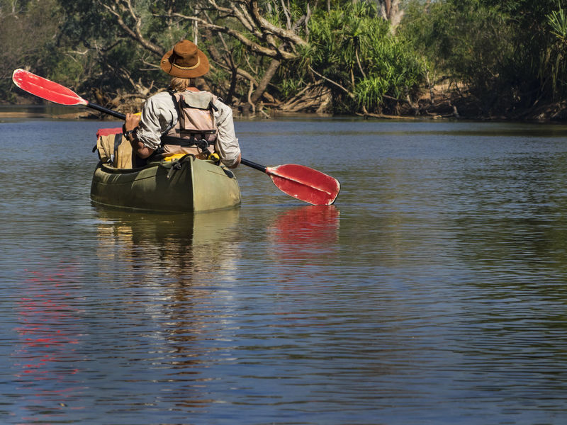 a women, wearing a life jacket and an cowboy hat is canoeing on a remote river Australian Landscape Northern Territory Adventure Canoe Kathrine River Kayak Leisure Activity Life Jacket Nature One Person Outdoors Paddling River