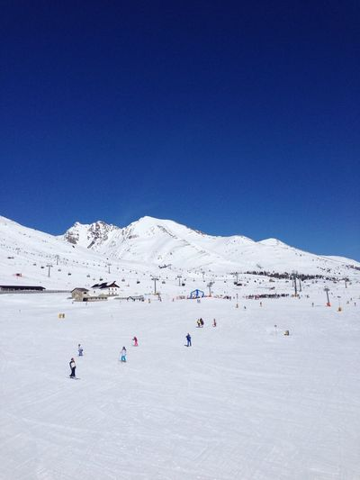 People skiing on snowcapped mountain against clear sky