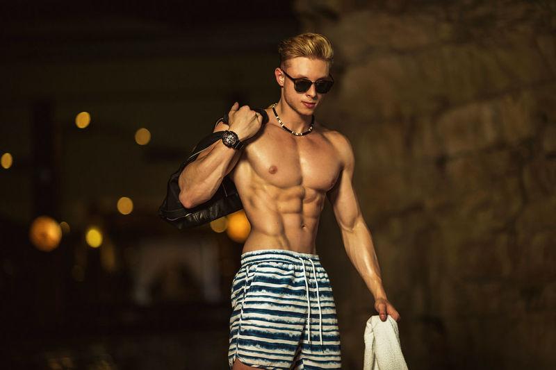 Shirtless muscular man standing at health spa