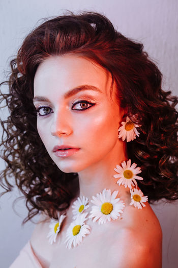 Close-up portrait of beautiful young woman wearing flowers and make-up