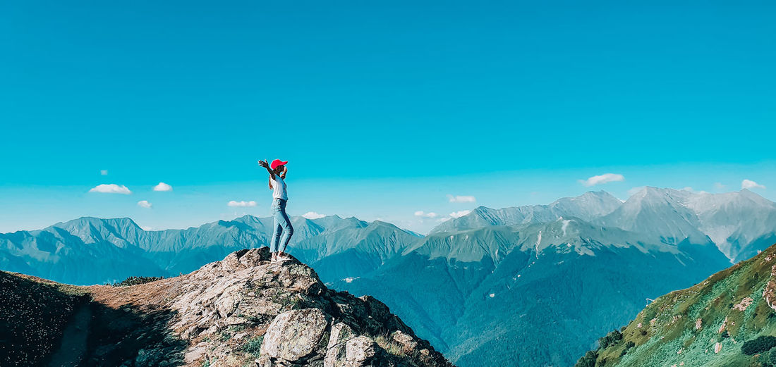 Woman standing on top of the mountain against blue sky