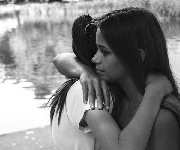 Side view of women hugging by lake